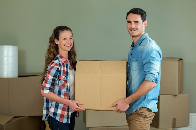 Young couple posing while unpacking carton boxes in new house