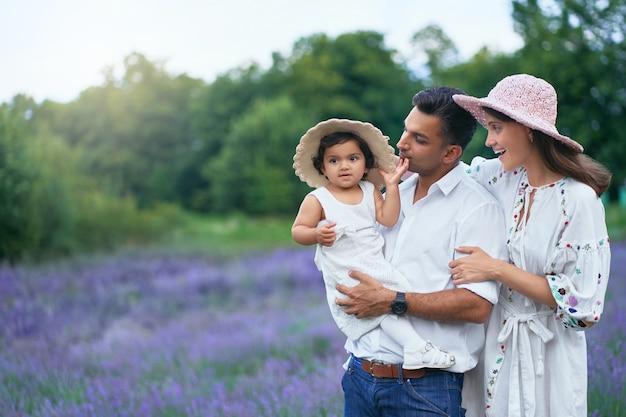 라벤더 밭에서 아이 함께 포즈를 취하는 젊은 부부