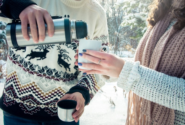 Young couple pours hot tea out of thermos in forest
