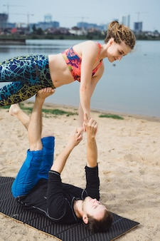 Young couple practicing yoga on city background