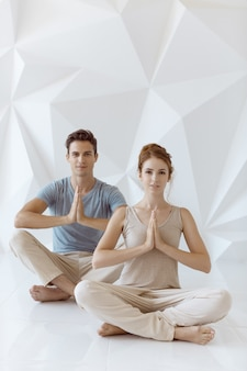 Young couple practicing yoga indoors on white abstract polygon background. young caucasian woman