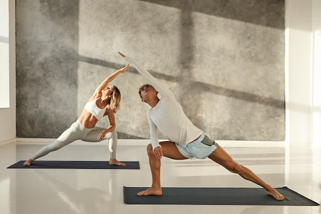 Young couple practicing yoga together. indoor picture of handsome tanned guy on mat doing standing pose s to strengthen legs, stretching arms and looking up