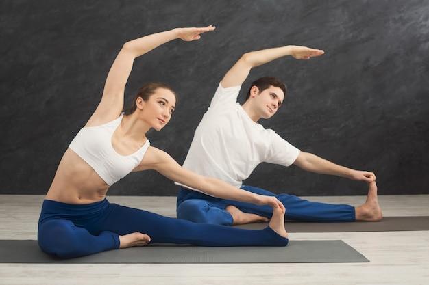 一緒にヨガを練習している若いカップル。マットの上に座ってストレッチ運動をしている男女、スペースをコピーします。パートナーヨガ、バランス、柔軟性のコンセプト