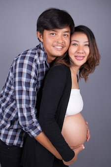 Young couple: pregnant mother and happy father on gray background