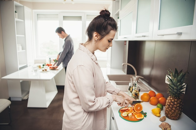 Молодая пара вместе готовит завтрак, нарезая фрукты на кухне