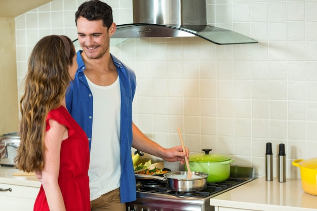 Young couple preparing food together in kitchen at home