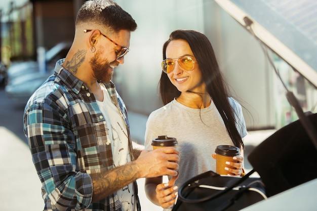 晴れた日に車で休暇旅行の準備をしている若いカップル。コーヒーを飲み、海や海に行く準備ができている女性と男性。