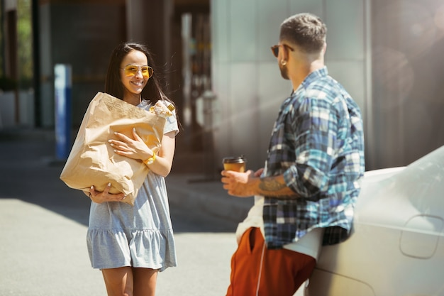 晴れた日に車で休暇旅行の準備をしている若いカップル。女性と男性が買い物をし、海、川沿い、または海に行く準備ができています。関係、休暇、夏、休日、週末の概念。