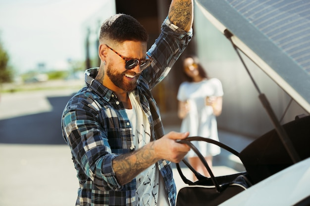 Молодая пара готовится к поездке в отпуск на машине в солнечный день. женщина и мужчина делают покупки и готовы к морю, реке или океану. концепция отношений, отпуск, лето, праздник, выходные.