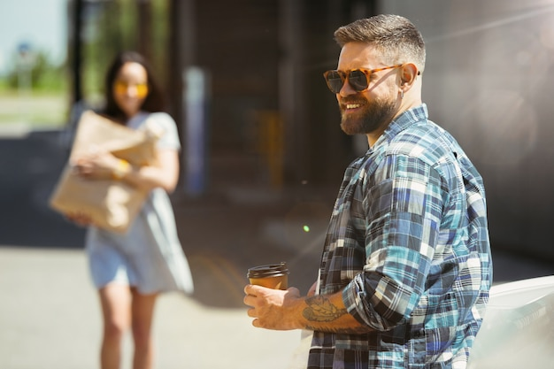晴れた日に車で休暇旅行の準備をしている若いカップル。女性と男性が買い物をし、海、川沿い、または海に行く準備ができています。