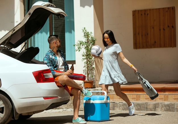 화창한 날에 차에 휴가 여행을 준비하는 젊은 부부. 여자와 남자 스포츠 장비를 쌓아. 바다, 강변 또는 바다에 갈 준비가되었습니다. 관계, 여름, 주말의 개념.