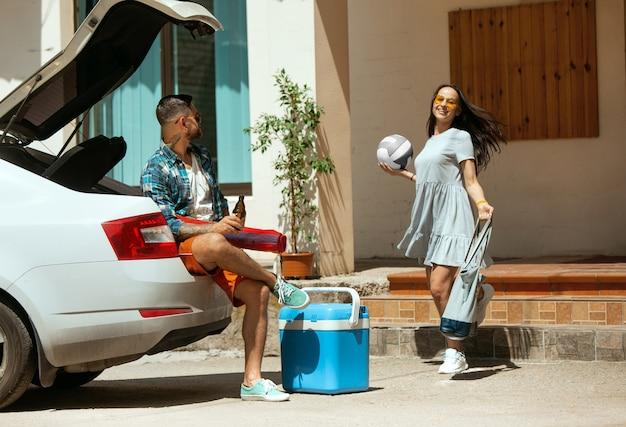Молодая пара готовится к поездке в отпуск на машине в солнечный день. женщина и мужчина складывают спортивное снаряжение. готовы к выходу к морю, реке или океану. концепция отношений, лето, выходные.