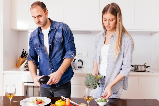 Young couple preparing salad with wineglasses on the wooden table