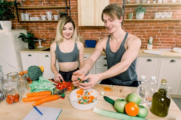 Молодая пара готовит салат на кухне. женщина молодого человека и светлых волос ослабляя и имея потеху с варить