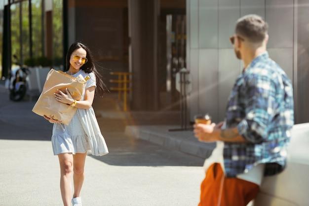 Giovani coppie che preparano per il viaggio di vacanza in macchina in una giornata di sole. donna e uomo che fanno shopping e pronti per andare in mare, lungo il fiume o sull'oceano.