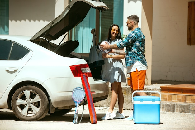 Young couple preparing for vacation trip on the car in sunny day. woman and man stacking up sport equipment. ready for going to sea, riverside or ocean. concept of relationship, summer, weekend.