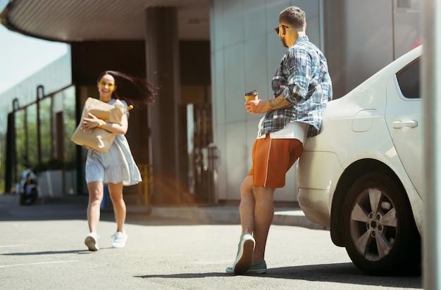 Giovani coppie che preparano per il viaggio di vacanza in macchina in una giornata di sole