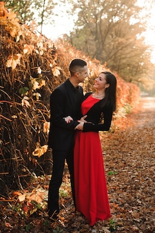 Young couple of pretty girl and man walk outdoors in park