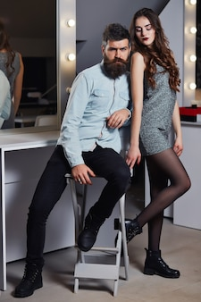 Young couple of pretty woman in gray dress and handsome bearded man with long beard