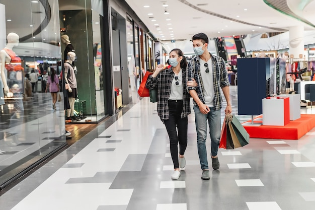 Young couple in protection mask holding multiple paper shopping bag walking in the corridor of large shopping mall