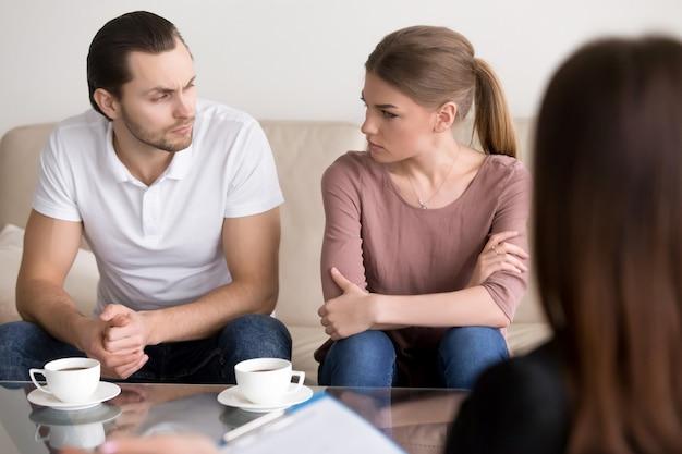 Giovani coppie allo psicologo, guardandosi l'un l'altro con odio