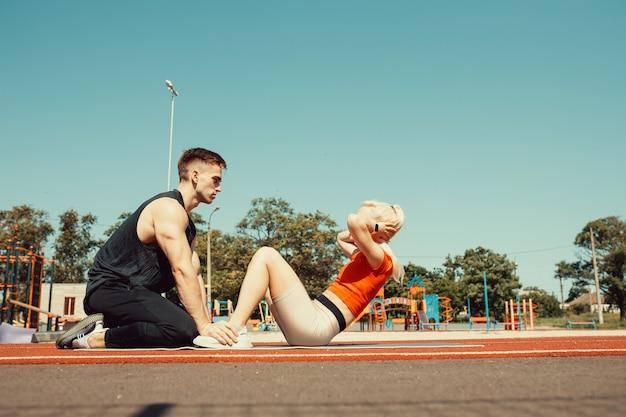Молодая пара накачивает мышцы живота на коврике для йоги