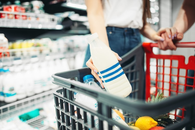 Young couple put bottle of milk into the cart, buyers in supermarket. customers in food store