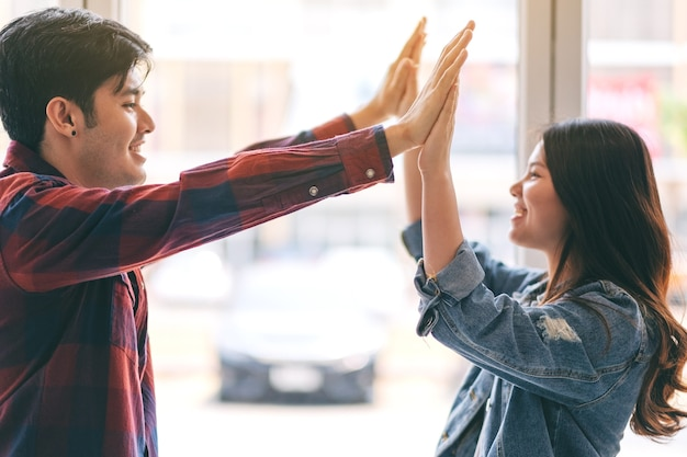 A young couple putting their hands to make high five to each other