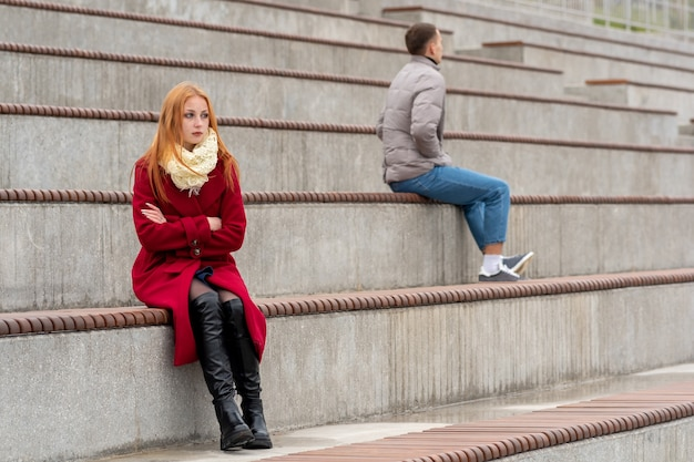 Young couple in a quarrel, a guy and a girl are sitting looking in different directions in the empty stands