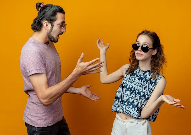 Giovane coppia litigare e gesticolare in piedi oltre il muro arancione