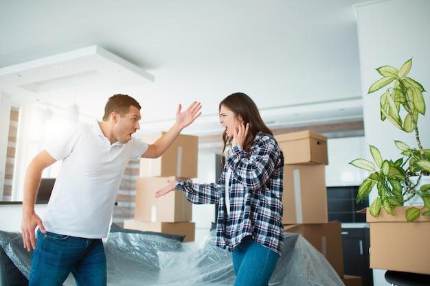 Молодая пара ссорится в новой квартире возле картонных коробок