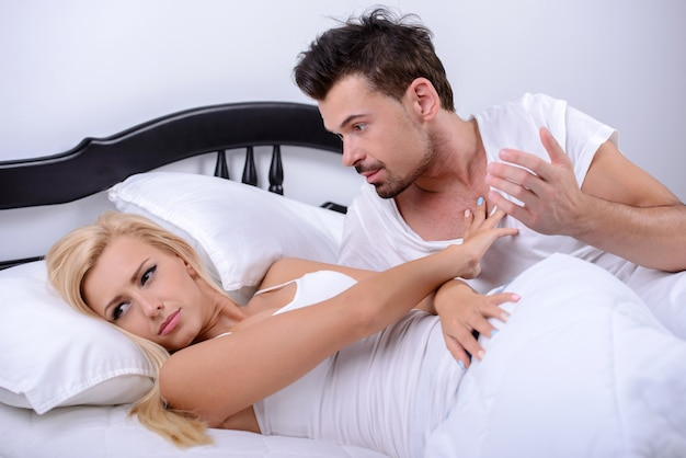 A young couple quarreling, lying in bed in her bedroom