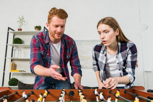 Young couple quarreling while playing the table soccer game