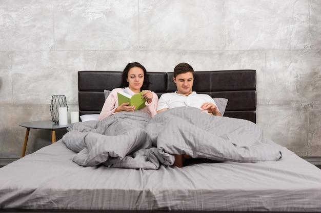 ベッドに横になって、灰色のロフトスタイルで寝室でパジャマを着て本を読んでいる若いカップル