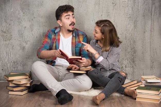 Giovani coppie che leggono un libro interessante e discutono