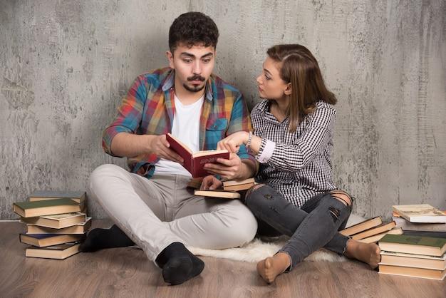 Giovani coppie che leggono un libro interessante mentre sedendosi sul pavimento