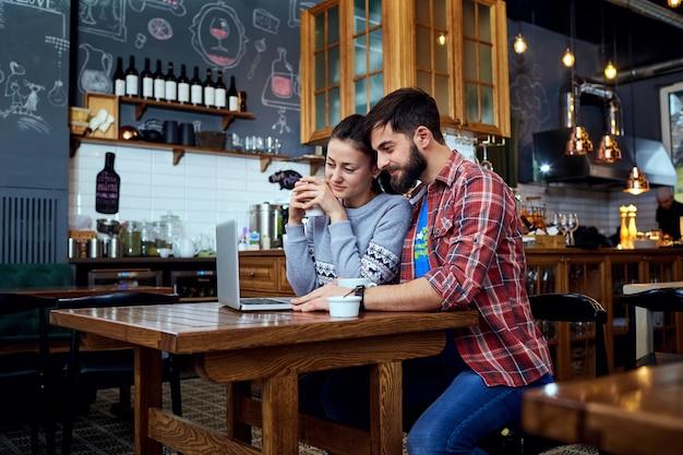 카페에서 노트북을보고 읽는 젊은 부부