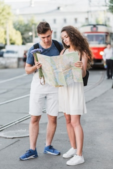 Young couple reading map on street