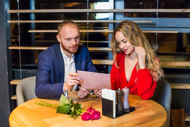 Young couple reading menu at table in restaurant