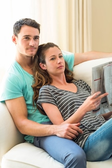 Young couple reading newspaper on sofa in living room