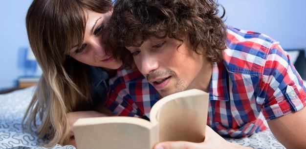ベッドに横たわっている本を一緒に読んでいる若いカップル