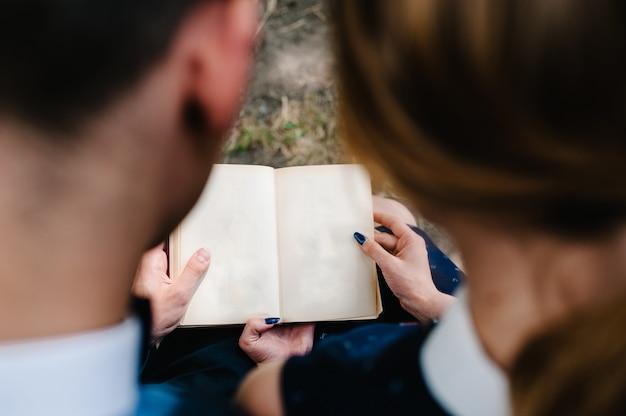 若いカップルが膝の上に開いた本を読む