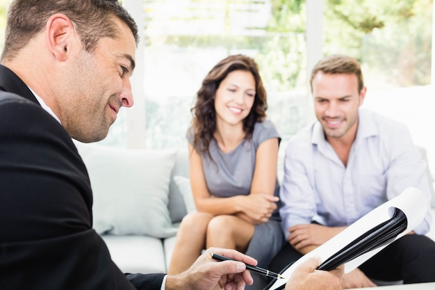 Young couple ready to buy new house interacting with estate-agent