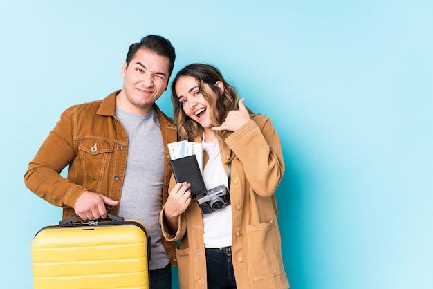 Молодая пара, готовая к путешествию, изолирована, показывая жест мобильного телефона пальцами.
