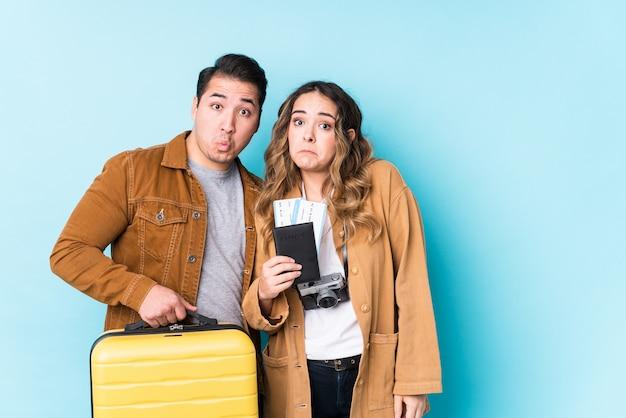 旅行の準備ができている若いカップルは肩をすくめ、開いた目は混乱しています。