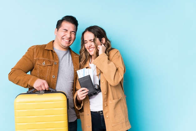 Young couple ready for a travel isolated covering ears with hands.