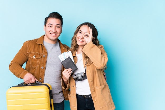 Young couple ready for a travel isolated excited keeping ok gesture on eye.