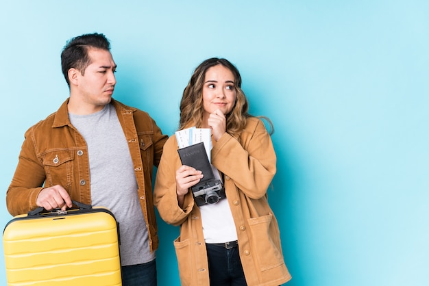 Young couple ready for a travel isolated looking sideways with doubtful and skeptical expression.