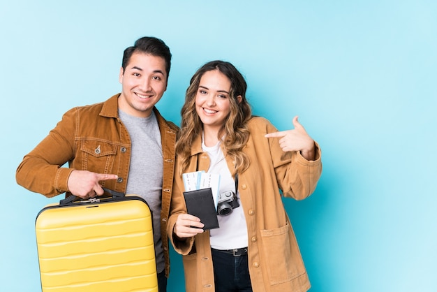 Young couple ready for a travel isolated person pointing by hand to a shirt copy space, proud and confident
