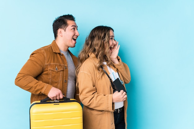 Young couple ready for a travel isolated shouting and holding palm near opened mouth.